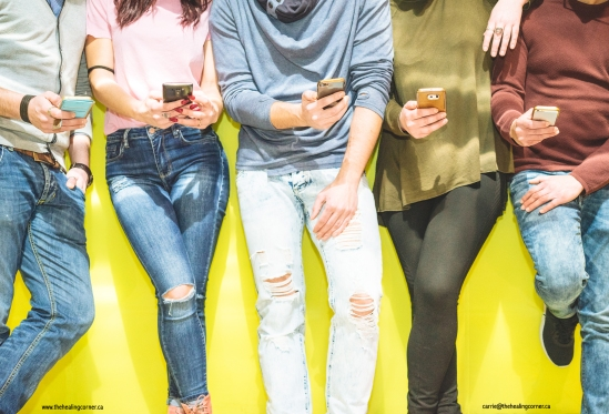 Group of friends having a social network moment watching on their mobile phones - People leaning on a yellow wall on their phones texting an